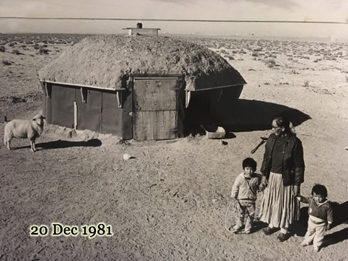 Mother and her daughter with a Navajo-Churro lamb at their hogan, 20 Dec 1981