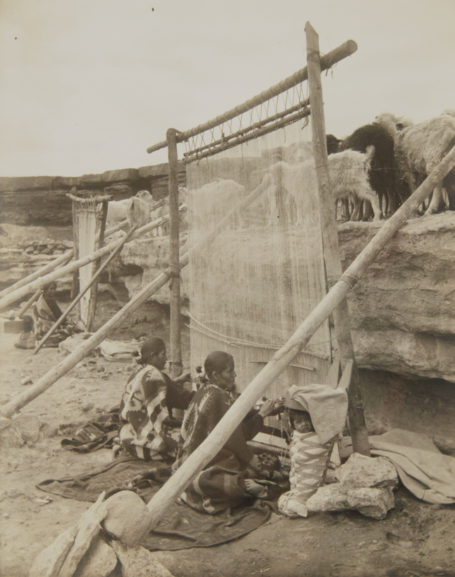 Navajo women surrounded by desert weave giant rugs below their sheep and goats